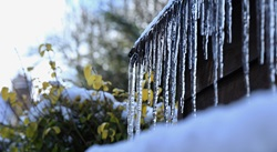 Thick icicles hanging from a roof in winter could be an indication of a damaging ice dam.